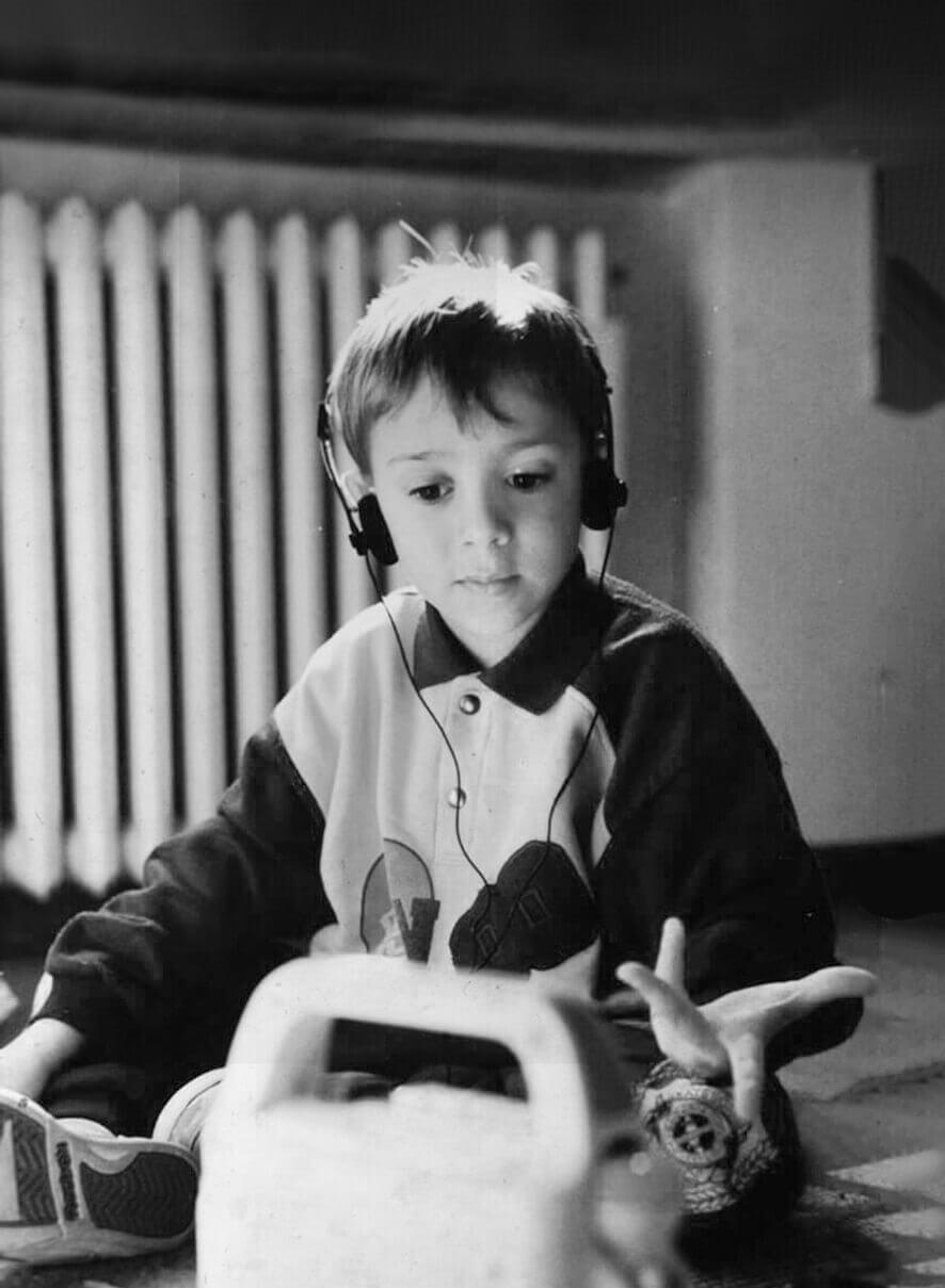 Alessandro Foschi da bambino che ascolta la musica con le cuffie, foto in bianco e nero