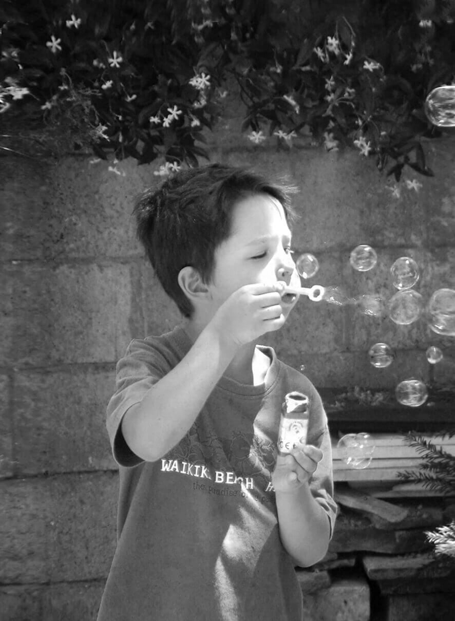 Lorenzo Lipparini da bambino mentre soffia le bolle di sapone, foto bianco e nero