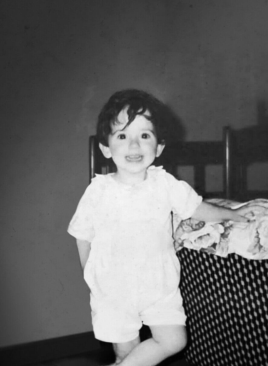 Manuela Di Benedetto da bambina dentro casa, mentre sorride in posa all'obiettivo. Foto in banco e nero