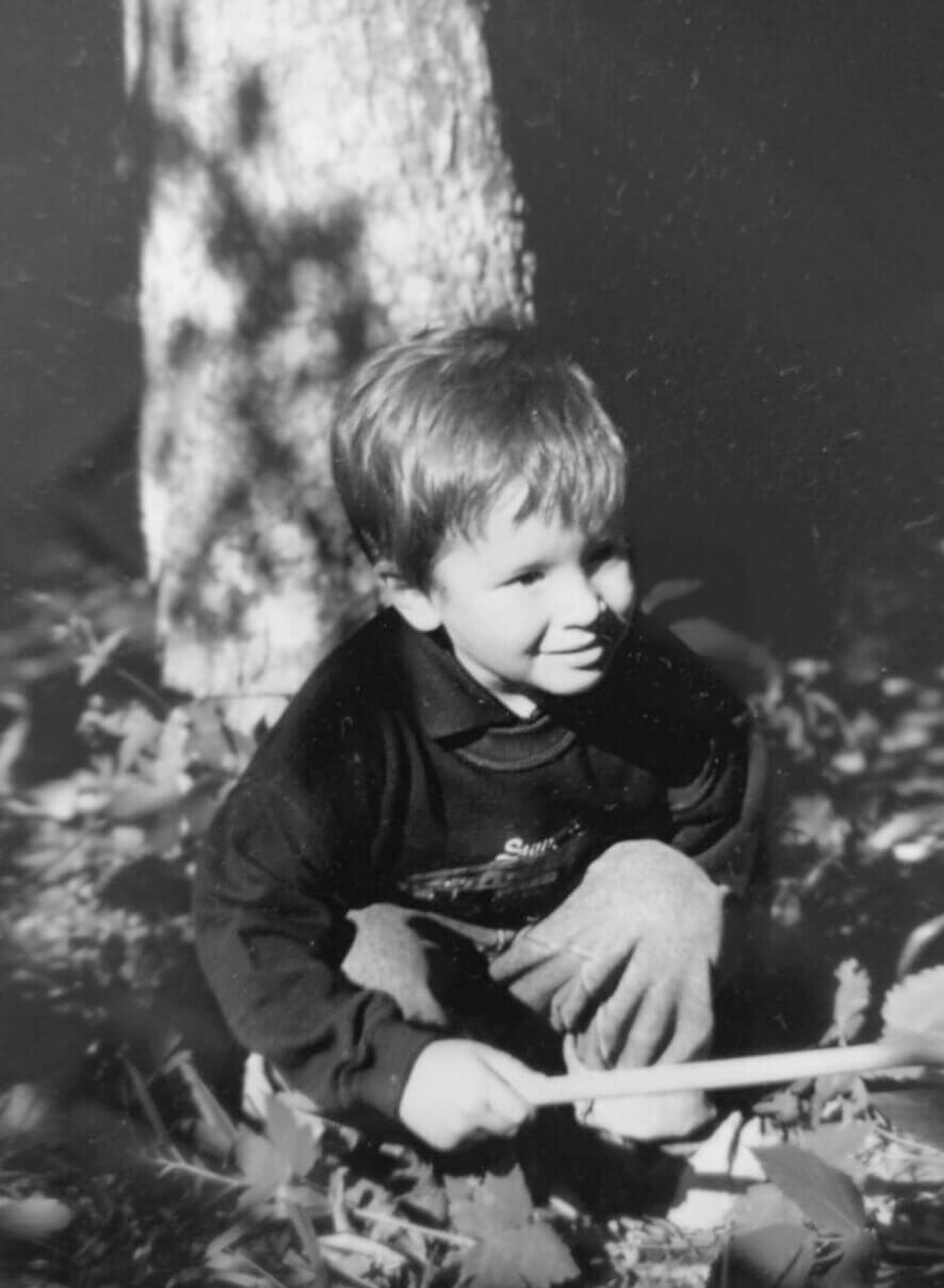 Stefano Valli da bambino accucciato in giardino con un ramo nella mano destra, foto in bianco e nero