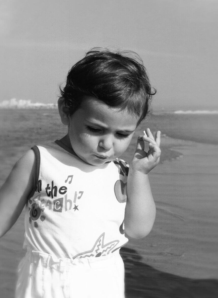 Lorenzo Vacchi da bambino, al mare porta una piccola conchiglia all'orecchio, foto in banco e nero