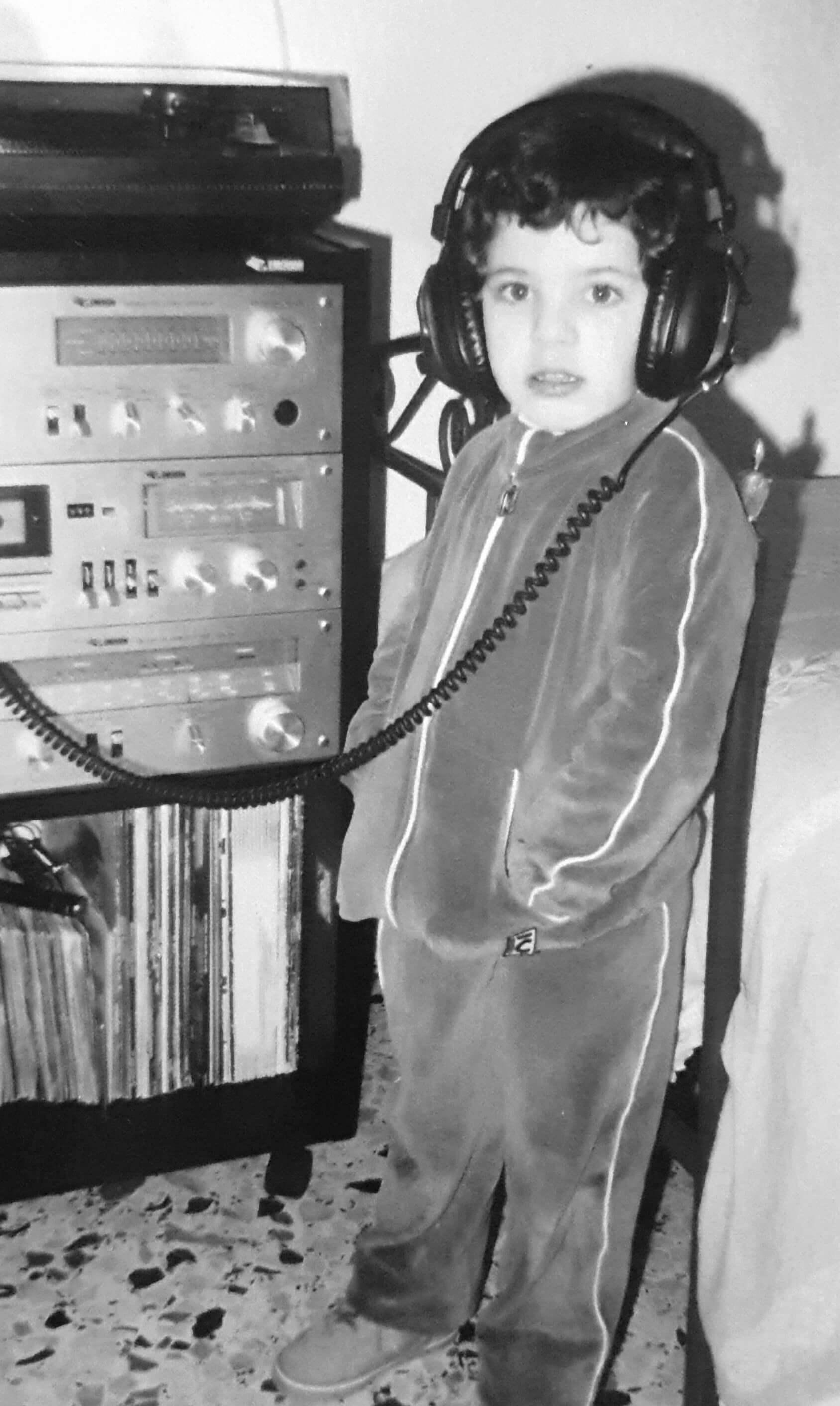 Biagio di Stefano da bambino mentre ascolta la musica dello stereo con le cuffie. Foto in bianco e nero.