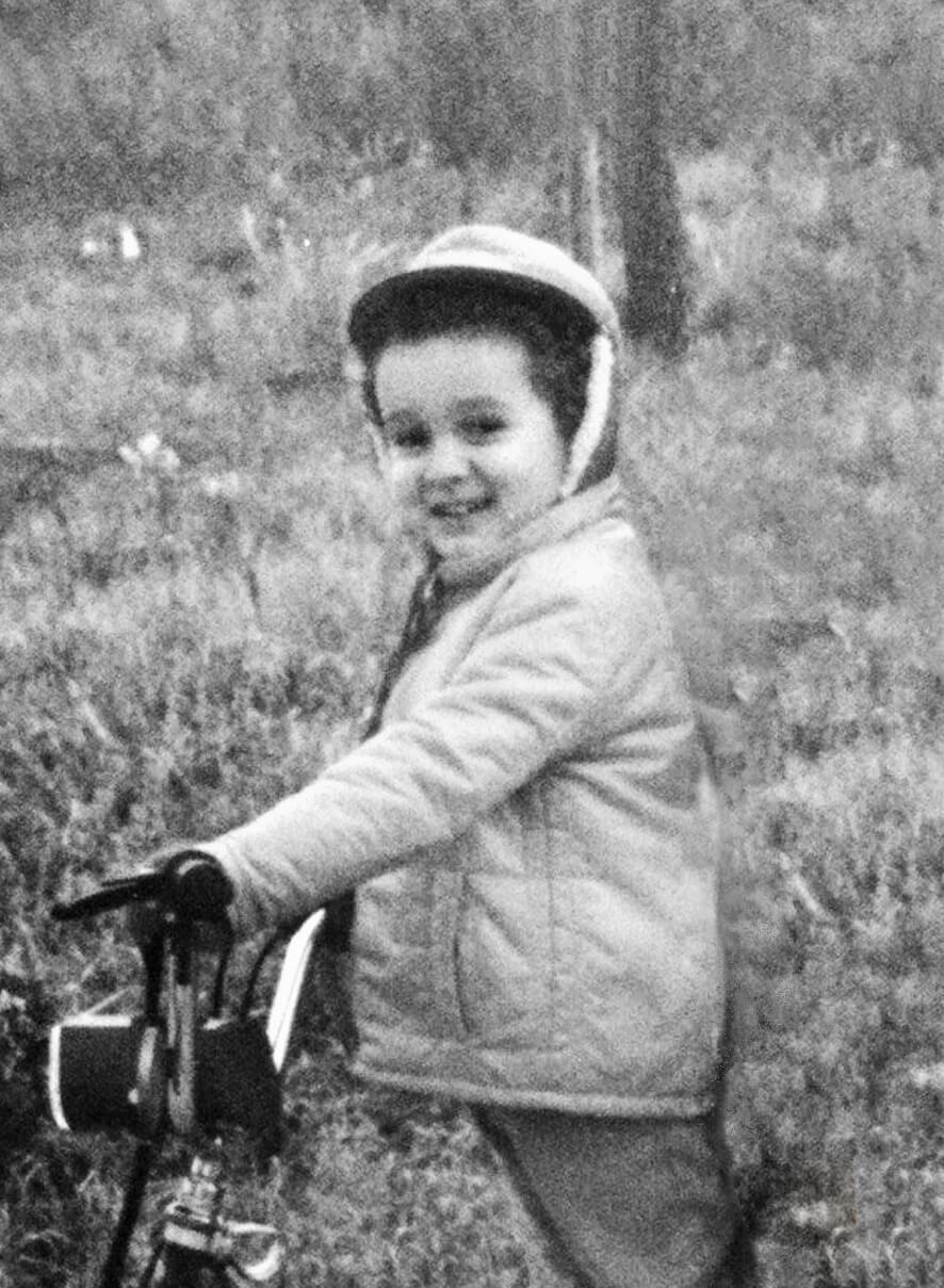 Paolo Bertazza da bambino mentre è in bicicletta. Foto in bianco e nero.